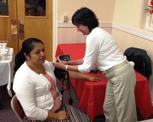 Ellen Oetinger, Community Volunteers in Medicine nurse, checks Antonia's blood pressure.