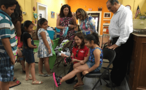 Ivonne, Arlete and Miguel look on as Griselle helps Mireya try on her new shoes.